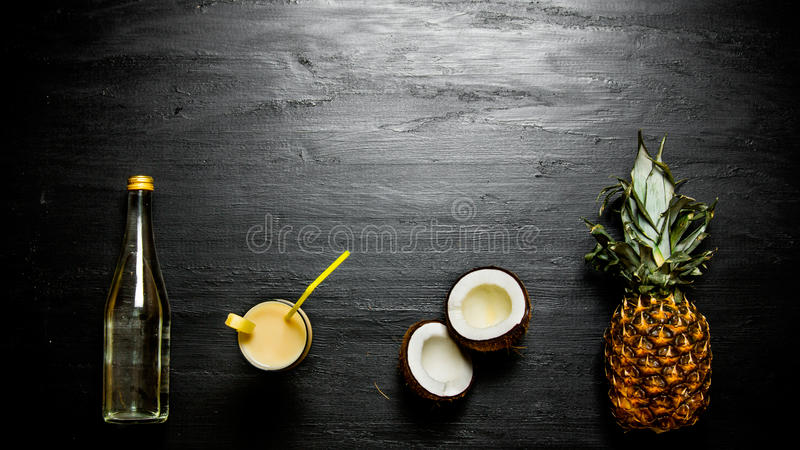 The ingredients for the cocktail - pineapple, coconut and a bottle of rum . Free space for text. stock image