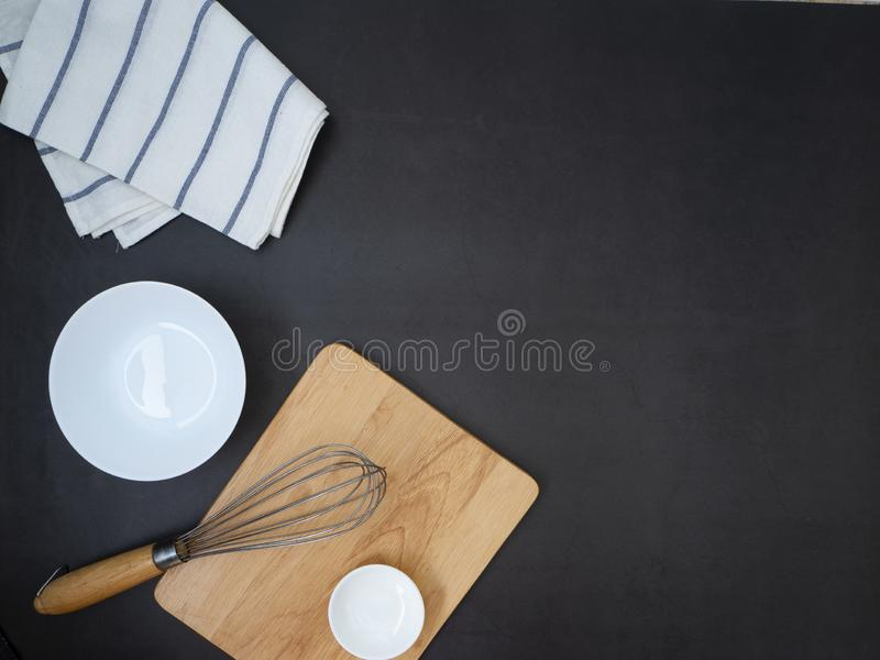 Ingredients concept of home cooking. Chopping Wood with Whisk and dish bowl on a dark granite table background. Copy space for text , Top view stock photography