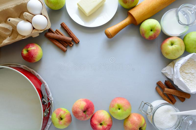 Ingredients for cooking apple pie. Fresh harvest apples, cinnamon, flour, sugar, butter, eggs, milk and baking mold royalty free stock images