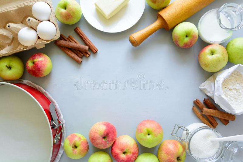 Ingredients for cooking apple pie. Fresh harvest apples, cinnamon, flour, sugar, butter, eggs, milk and baking mold. On gray wooden background. Top view. Flat royalty free stock photos