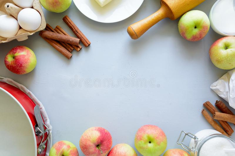 Ingredients for cooking apple pie. Fresh harvest apples, cinnamon, flour, sugar, butter, eggs, milk and baking mold. On gray wooden background. Top view. Flat royalty free stock photo