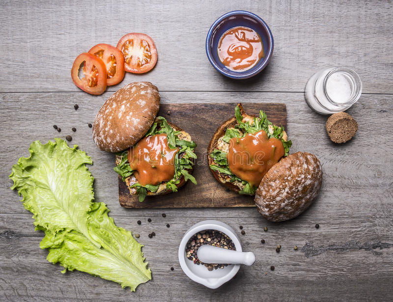 Ingredients for cooking a burger with chicken and vegetables, peppers, tomatoes, lettuce and salt on wooden rustic background top stock photo
