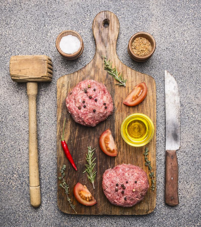 Ingredients for cooking burgers, ground beef, tomatoes, red pepper and other spices laid out on cutting board with a knife and a. Ingredients for cooking burgers stock photo