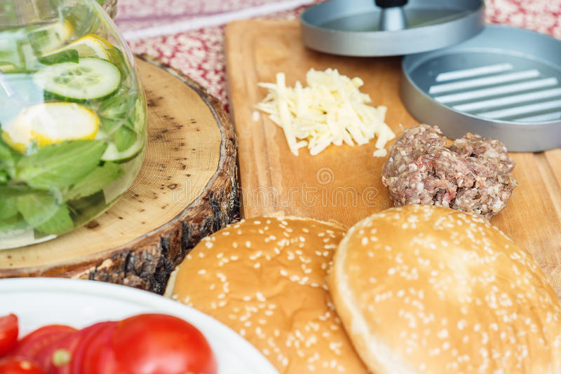 Ingredients for cooking burgers. Raw ground beef meat cutlets on wooden chopping board, red onion, cherry tomatoes, greens, cheese royalty free stock photos