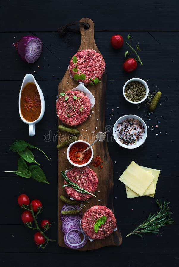 Ingredients for cooking burgers. Raw ground beef meat cutlets on wooden chopping board, red onion, cherry tomatoes royalty free stock image