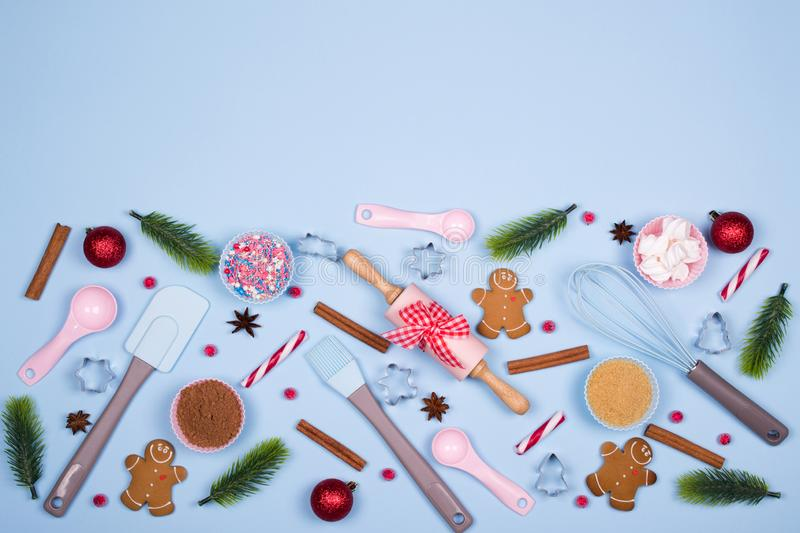 Ingredients for cooking christmas cookies, kitchen utensils, gingerbread cookies on blue pastel background. royalty free stock image