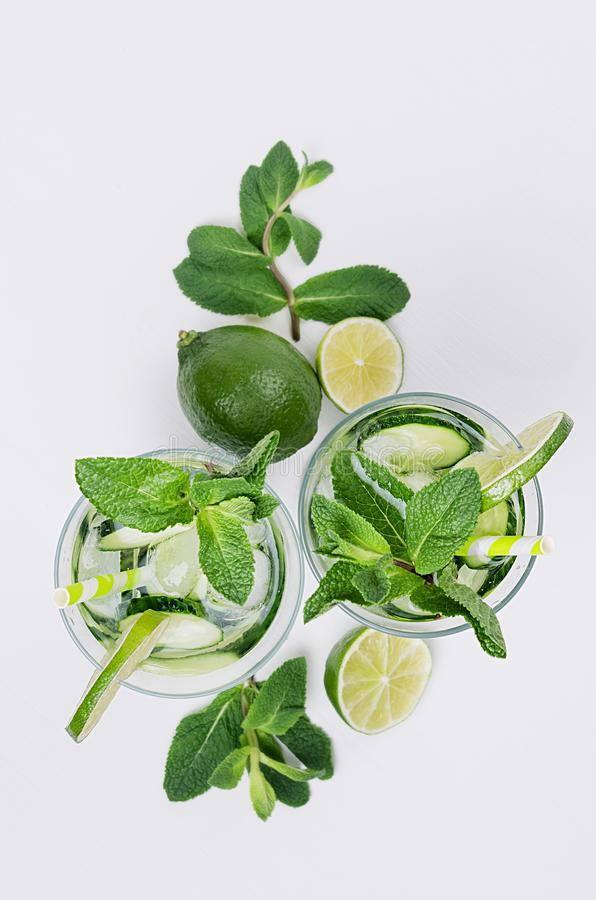 Ingredients for cooking cold spring drink with cucumber, pieces of lime, fresh leaves mint and ice cubes on soft white background. stock photo