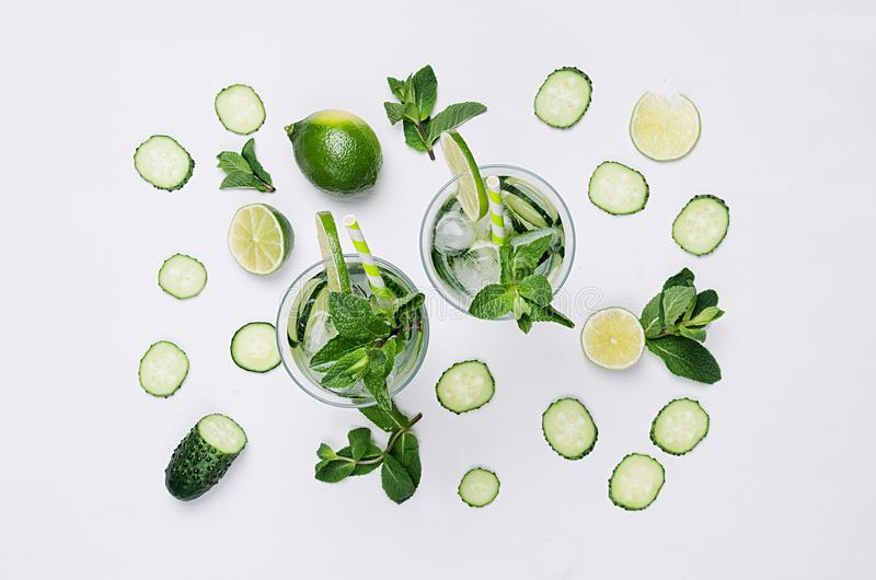 Ingredients for cooking cold spring drink with cucumber, pieces of lime, fresh leaves mint and ice cubes on soft white background. royalty free stock image
