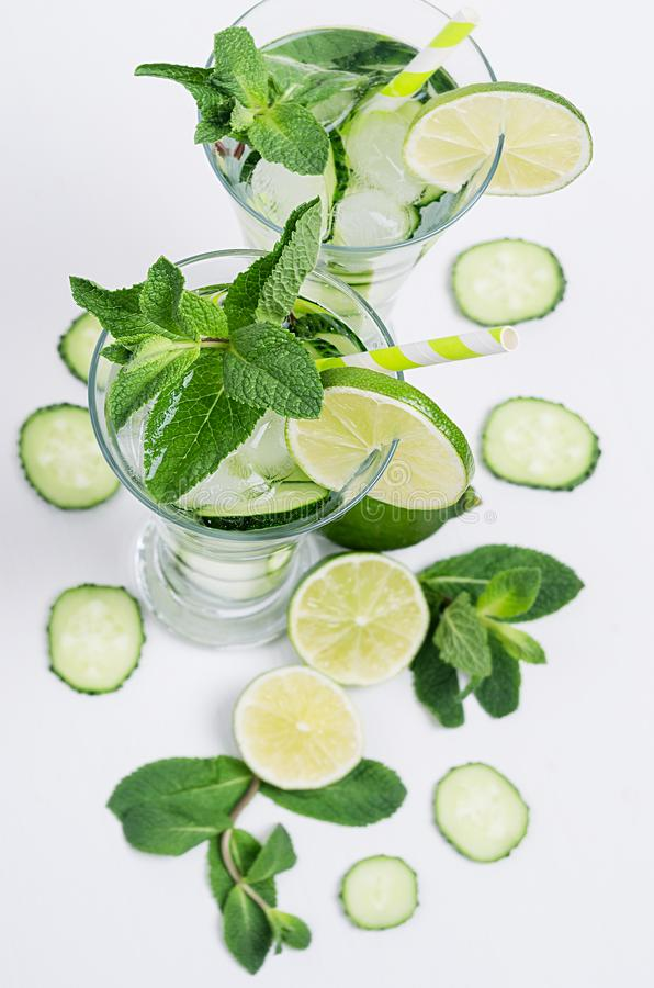 Ingredients for cooking cold spring drink with cucumber, pieces of lime, fresh leaves mint and ice cubes on soft white background. stock image