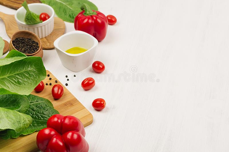 Ingredients for cooking fresh raw spring salad of green and red vegetables, spices, oil with wooden kitchenware on white wood back. Ground, border stock photography