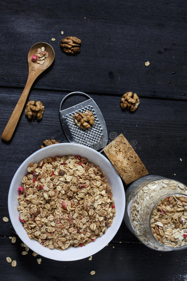Ingredients for cooking healthy breakfast. Nuts, oat flakes, dried fruits, honey, granola, wooden heart in a white bowl. stock images