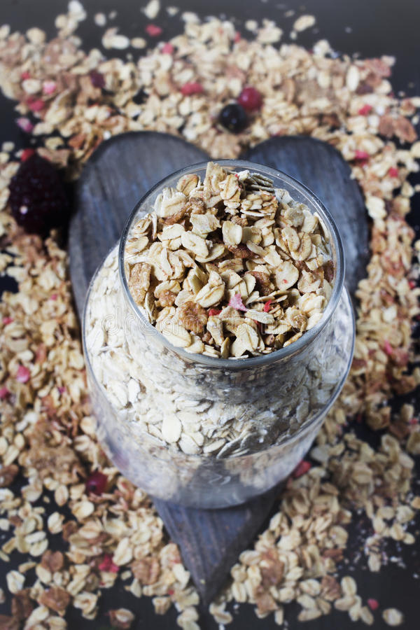 Ingredients for cooking healthy breakfast. Nuts, oat flakes, dried fruits, honey, granola, wooden heart . stock photo