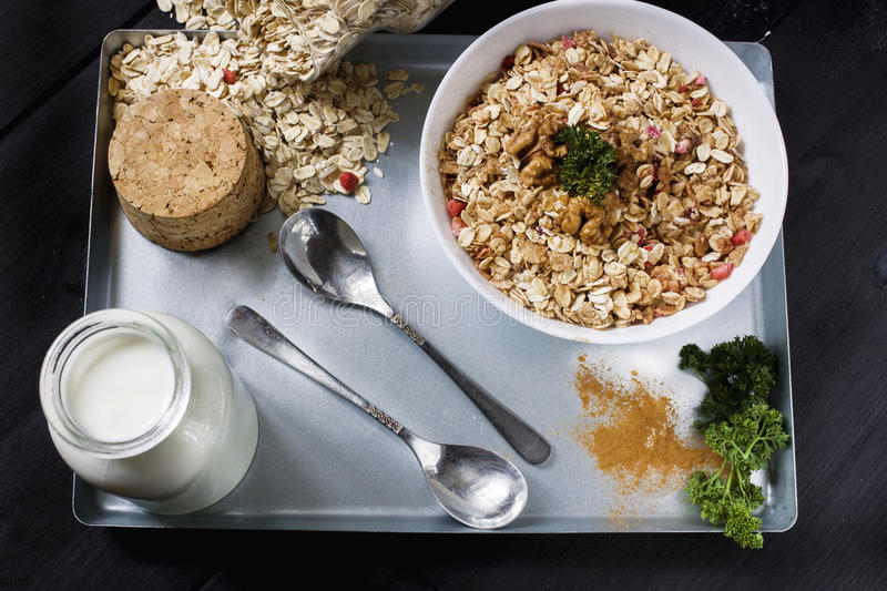 Ingredients for cooking healthy breakfast. Nuts, oat flakes, dried fruits, honey, granola, wooden heart in a white bowl. royalty free stock photo