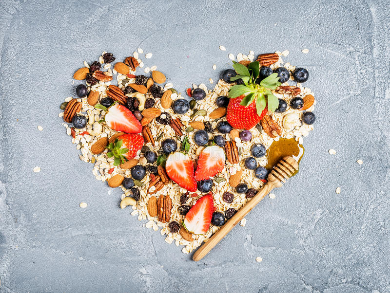Ingredients for cooking healthy breakfast in shape of heart. Strawberries, blueberries, nuts, oat flakes, dried fruits stock photos