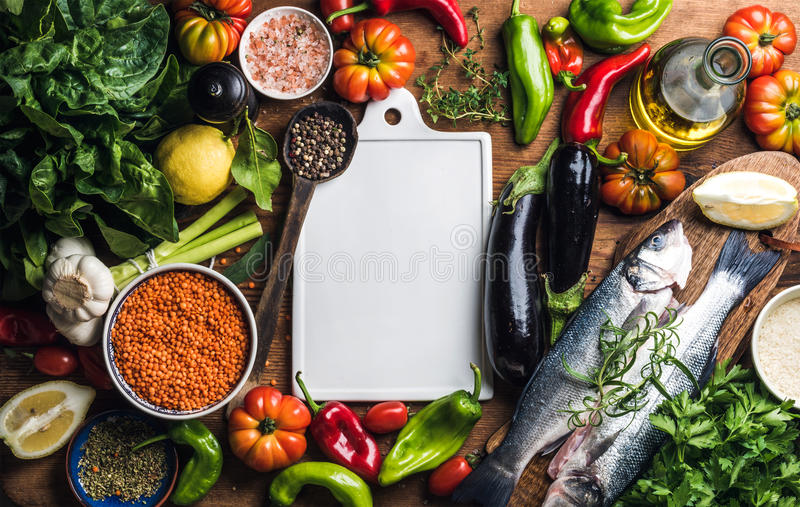 Ingredients for cooking healthy dinner. Raw uncooked seabass fish with vegetables, grains, herbs and spices over rustic. Wooden background, white ceramic board stock images