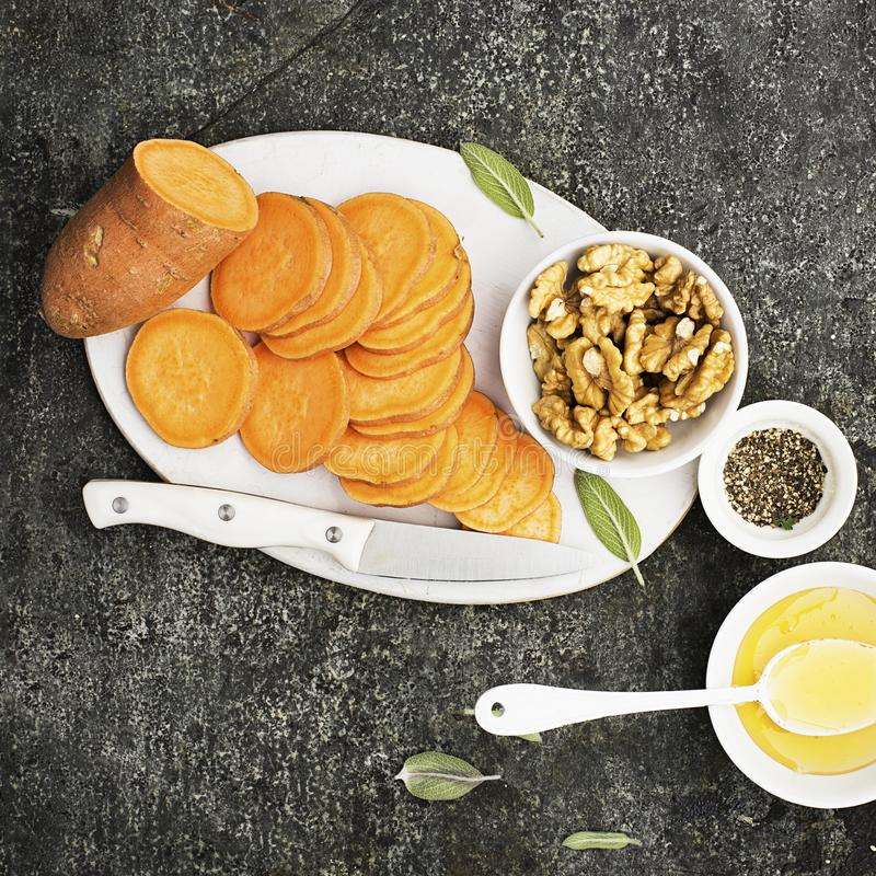 Ingredients for cooking healthy simple snacks from slices of sweet potato, walnuts with honey before baking. Top view royalty free stock photo