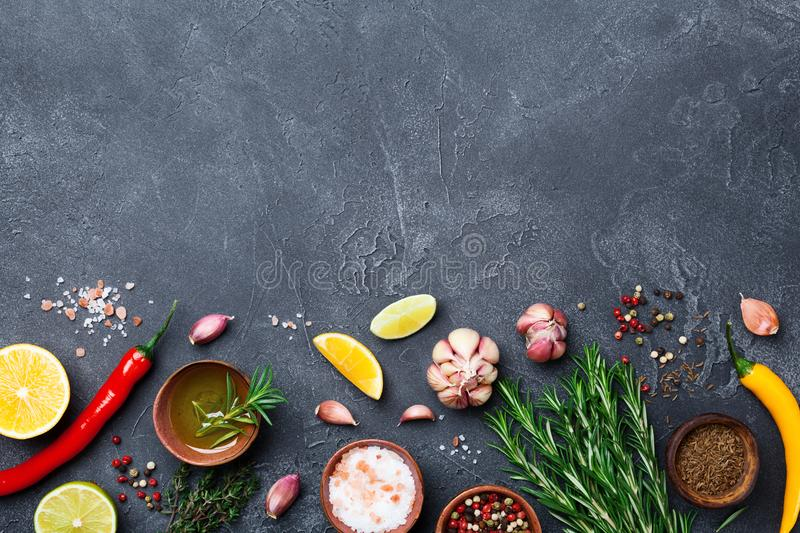 Ingredients for cooking. Herbs and spices on black stone table top view. Food background. royalty free stock image