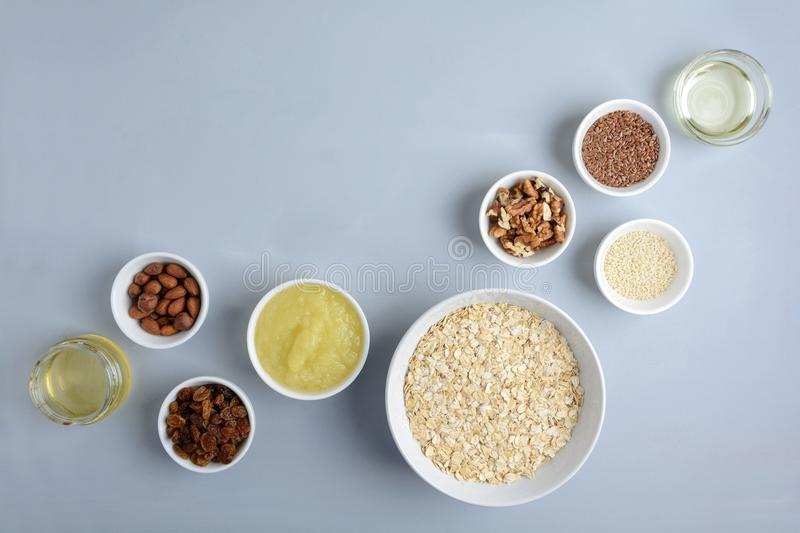 Ingredients for cooking homemade granola: oatmeal, applesauce, honey, oil, almond, walnut, raisin, flax and sesame seeds. On wooden gray background. Flat lay royalty free stock image