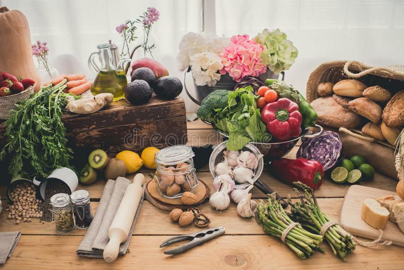 Ingredients for cooking. On a wood table, different kind of breads, nuts, olive oil, avocados, carrots, ginger, red pepper, lettuce, broccoli, garlic, nuts royalty free stock images