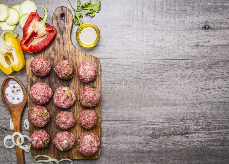 Ingredients for cooking meat balls with herbs and onions on a cutting board with tomatoes, peppers, zucchini and herbs on wooden r. Ingredients cooking meat royalty free stock photo