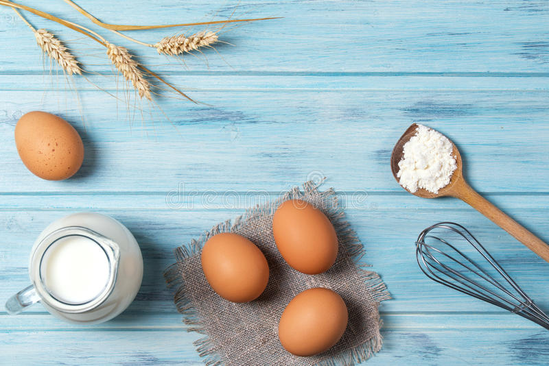 Ingredients for cooking, milk, eggs, wheat flour and kitchenware on blue wooden background, top view royalty free stock images