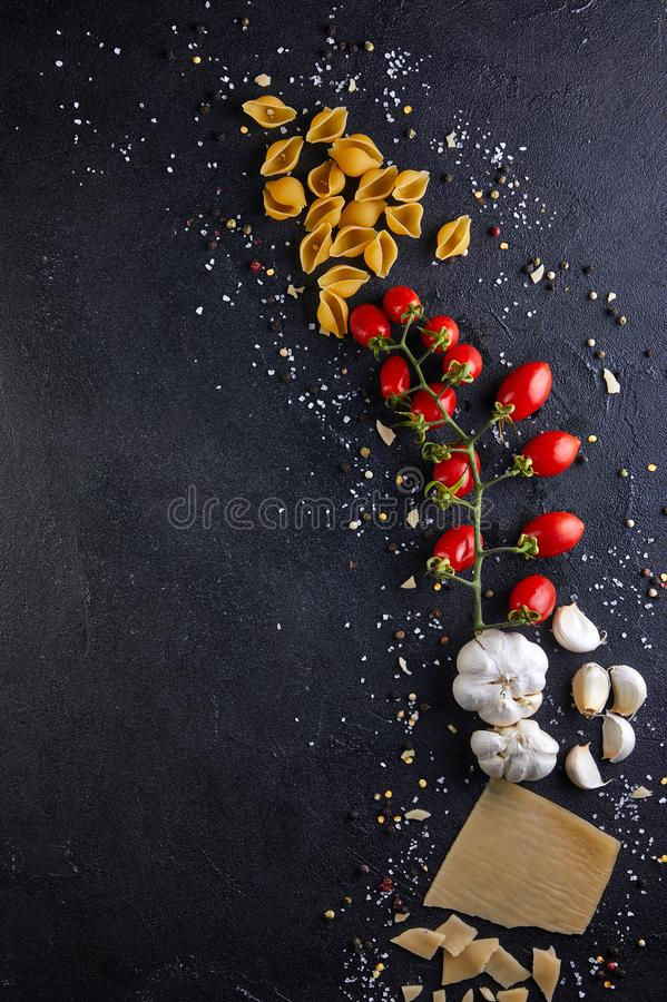 Ingredients for cooking pasta on a black background. Pasta, sherry tomatoes, garlic, cheese, pepper and salt, italian, italy, vegetarian, food, macaroni stock photography