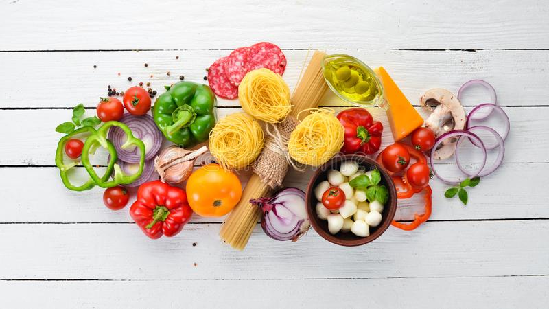 Ingredients for cooking pasta. Dry pasta. Mushrooms, sausages, tomatoes, vegetables. royalty free stock photos