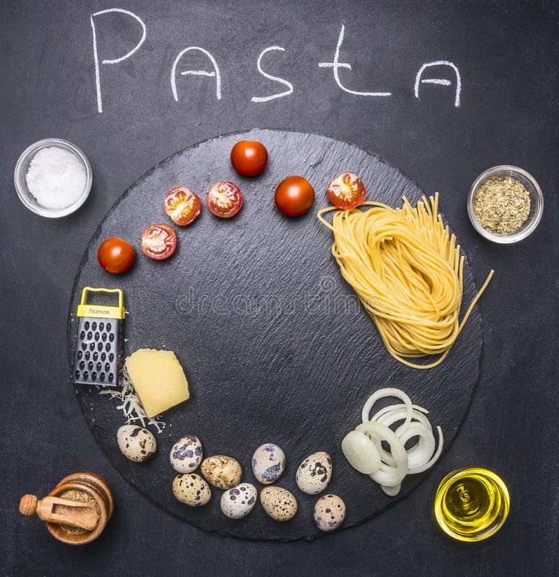 Ingredients for cooking pasta with quail eggs and parmesan cheese and cherry tomatoes, spices and oil on rustic black backgro royalty free stock images