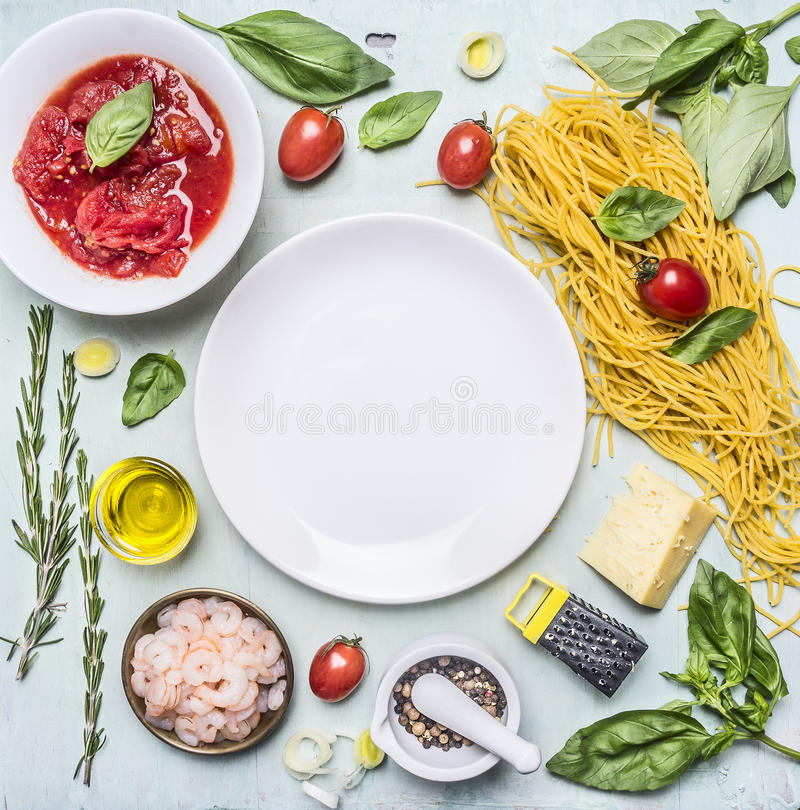 Ingredients for cooking pasta, tomatoes in own juice, basil, shrimp, grater, cherry tomatoes, laid around a white plate place stock photos