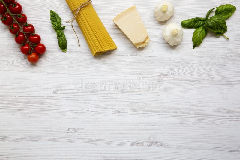 Ingredients for cooking pasta on a white wooden background. royalty free stock image