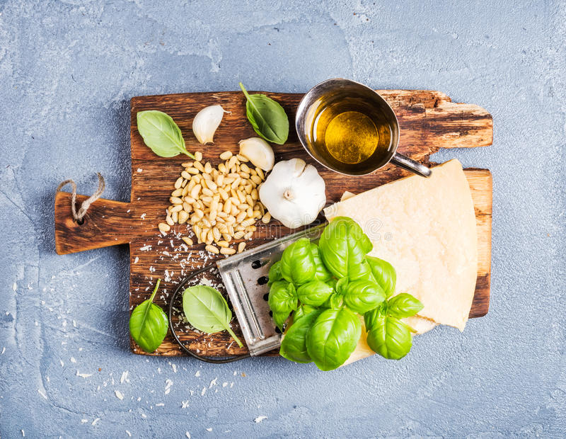 Ingredients for cooking Pesto sauce. Parmesan cheese, metal grater, fresh basil, olive oil, garlic and pine nuts on old royalty free stock photo