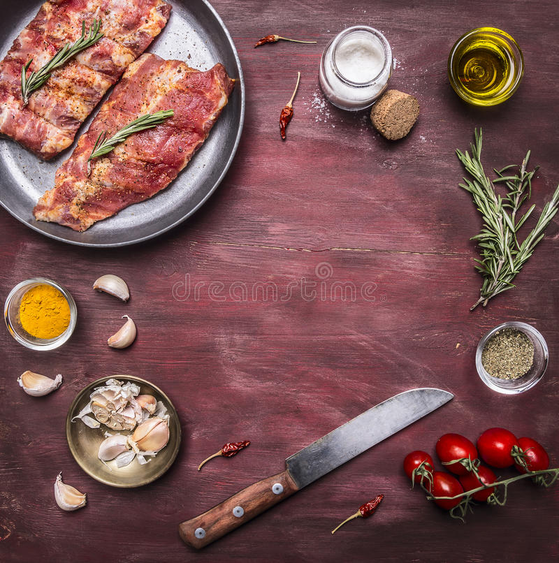 Ingredients for cooking raw lamb ribs in a pan with herbs, a knife, seasoning, tomatoes place for text,frame on wooden rustic back. Ingredients cooking raw lamb royalty free stock photography