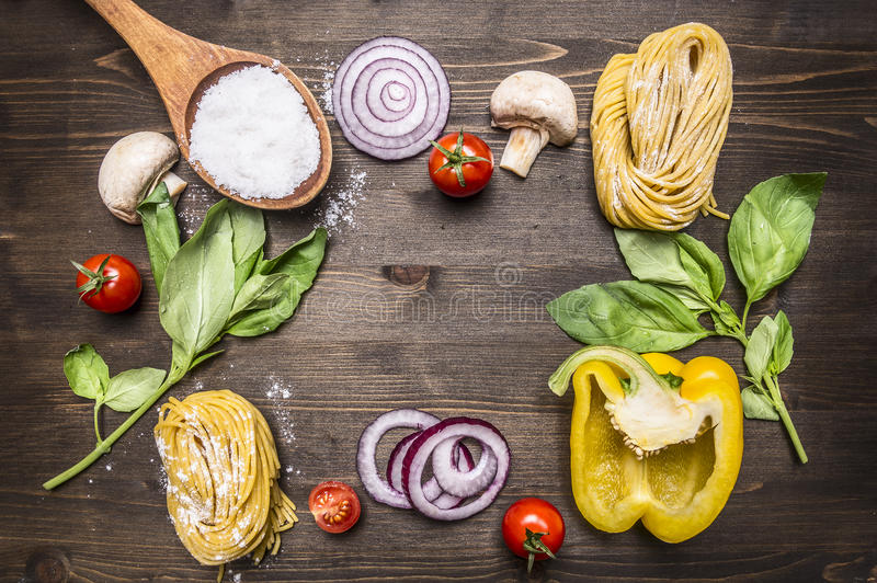 Ingredients for cooking raw pasta with mushrooms, peppers, basil and onions on wooden rustic background top view close up border, royalty free stock photos