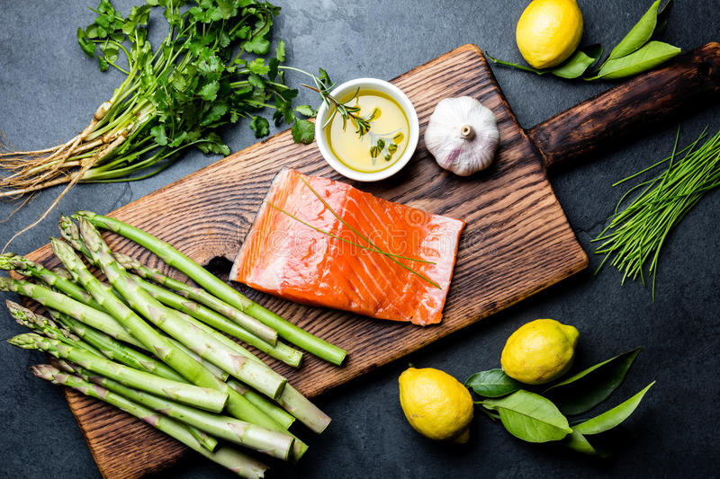 Ingredients for cooking. Raw salmon fillet, asparagus and herbs on wooden board. Food cooking background with copy space royalty free stock photo