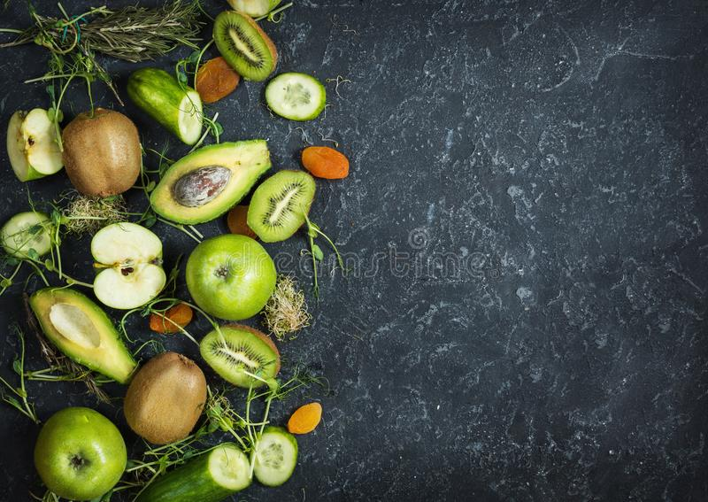 Ingredients for cooking smoothie. Organic green vegetables and fruits on black stone background. Copy space, top view royalty free stock photos