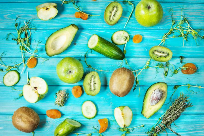 Ingredients for cooking smoothie. Organic green vegetables and fruits on blue wood background. Flat lay stock photography