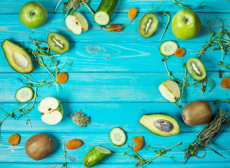 Ingredients for cooking smoothie. Organic green vegetables and fruits on wooden blue rustic background. Copy space, flat stock images