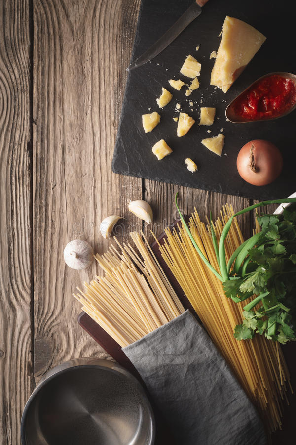 Ingredients for cooking spaghetti with cheese and fresh herbs on the old table royalty free stock images