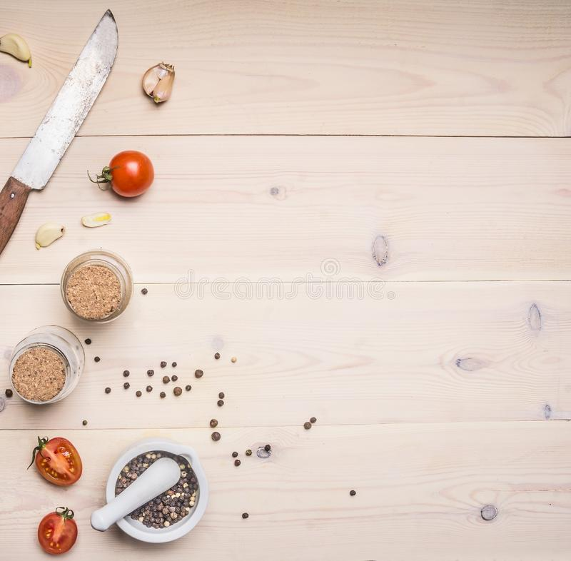 Ingredients for cooking spices, knife, salt and pepper shakers, cherry tomatoes on white wooden rustic background, space for te. Ingredients for cooking spices stock photo