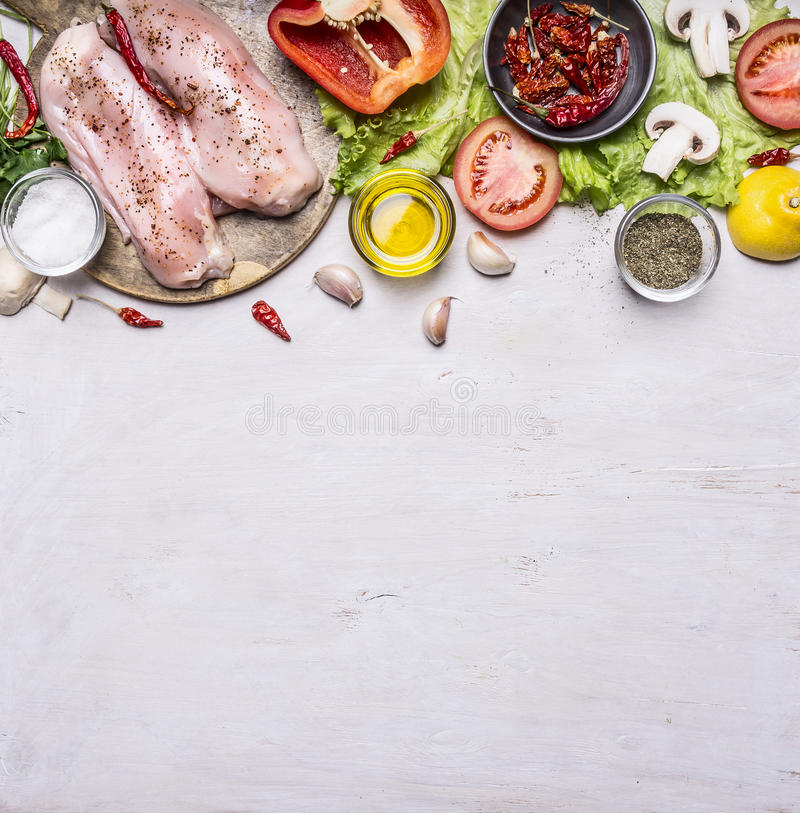 Ingredients for cooking a turkey breast On a cutting board pepper oil tomato chili lemon lettuce mushrooms salt spices laid stock photo
