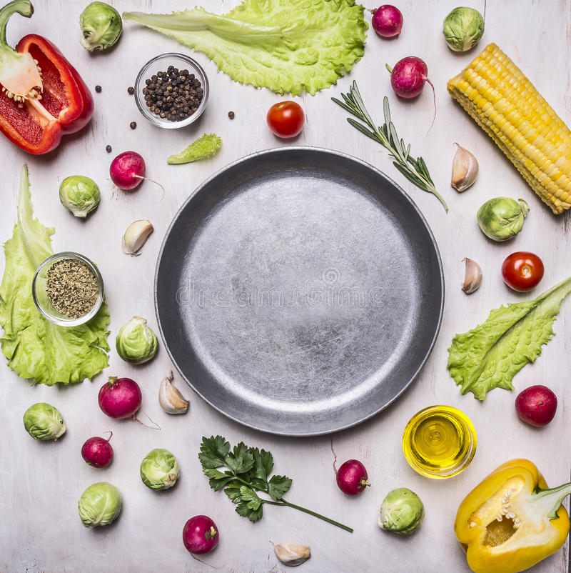 Ingredients for cooking vegetarian food, corn, radishes, rosemary, pepper, oil, seasonings, lined around pan place for text,fr. Ingredients for cooking stock images