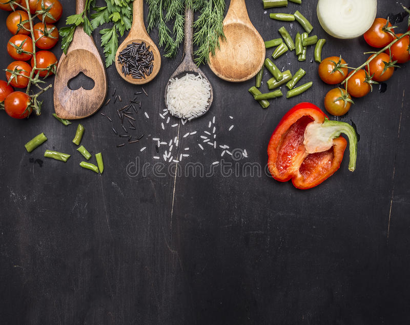 Ingredients for cooking vegetarian food wooden spoons, cherry tomatoes, dill, parsley, pepper border ,place text on wooden ru stock images