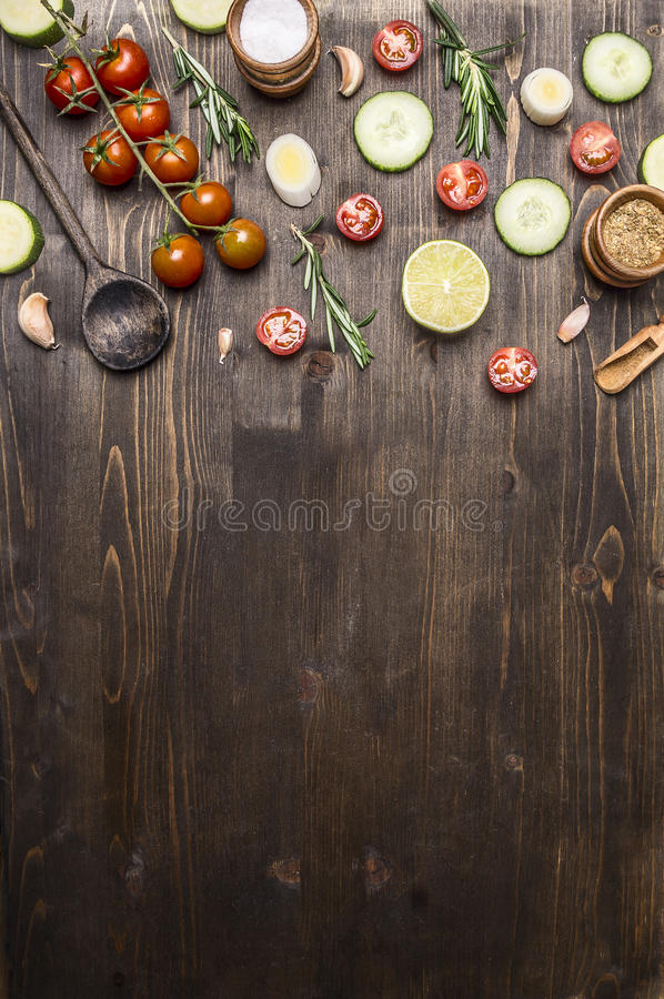 Ingredients for cooking vegetarian food wooden spoons, cherry tomatoes, dill, parsley, pepper border ,place text on wooden ru stock photos