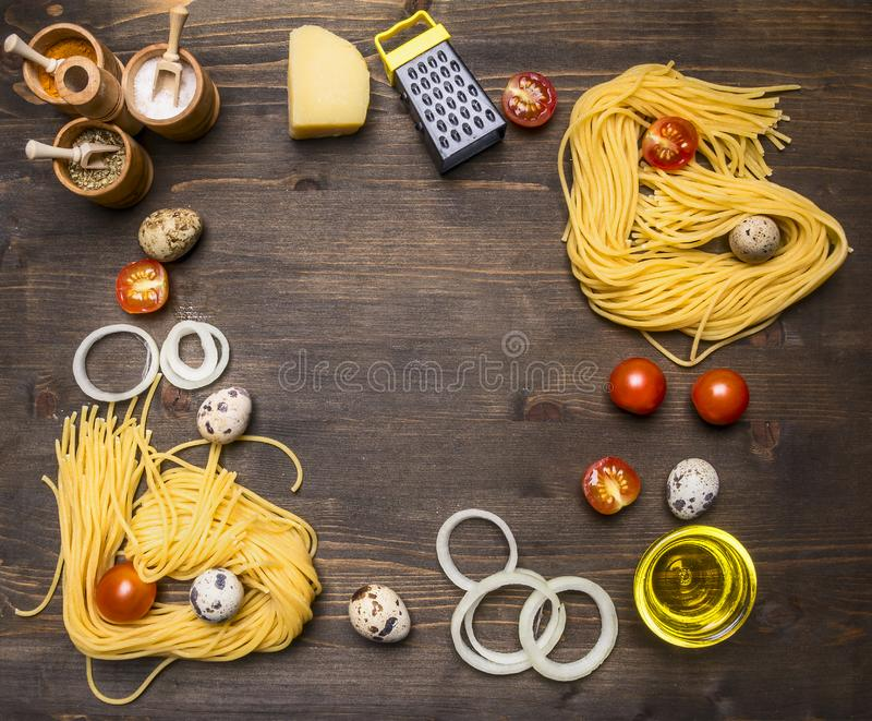 Ingredients for cooking vegetarian pasta with cherry tomatoes, onions, parmesan cheese, a variety of spices rustic wooden backg royalty free stock images