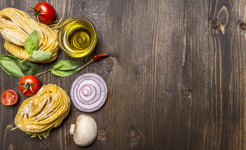 Ingredients for cooking vegetarian pasta on wooden rustic background top view close up border ,with text area royalty free stock images