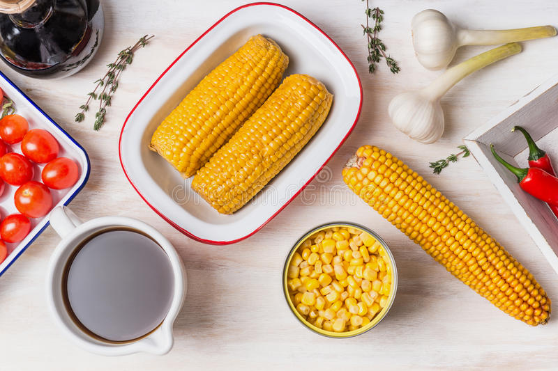 Ingredients for corn soup or stew: ear of corn, canned and cooked corn , seasoning and vegetables broth on white wooden background stock photos