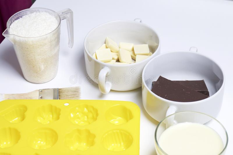 Ingredients for dessert are on the table. Cooking sweets with coconut and condensed milk. In a glaze of white and black chocolate.  stock photography