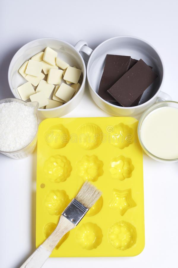 Ingredients for dessert are on the table. Cooking sweets with coconut and condensed milk. In a glaze of white and black chocolate stock images