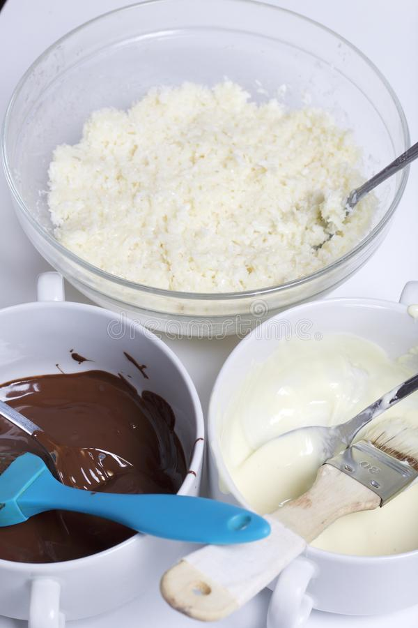 Ingredients for dessert are on the table. Cooking sweets with coconut and condensed milk. In a glaze of white and black chocolate royalty free stock photography