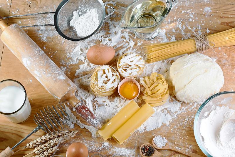 Ingredients for dough, cooking pasta tagliatelle spaghetti, including flour, eggs, milk, on wooden rustic background, top view, se royalty free stock photo
